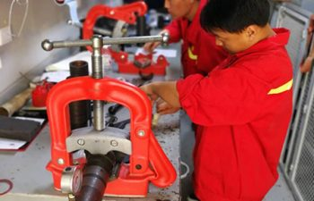 Asian drilling team servicing the equipment at the workshop in China.